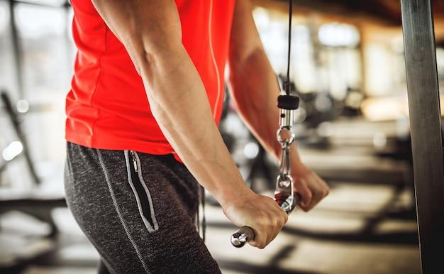 Schließen sie herauf ansicht der männerhände, die metallstange auf der maschine im fitnessstudio nach unten drücken.
