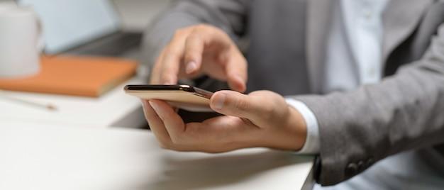 Schließen sie herauf ansicht der männlichen hände unter verwendung des smartphones beim sitzen am weißen schreibtisch