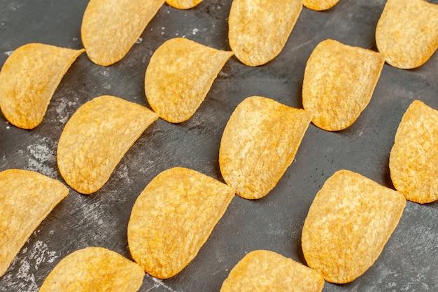 Schließen sie herauf ansicht der snack-party für freunde mit leckeren kartoffelchips auf grauem tisch