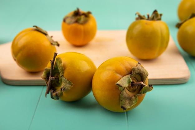 Schließen sie herauf ansicht der unreifen kaki-früchte auf einem hölzernen küchenbrett auf einer blauen holzwand