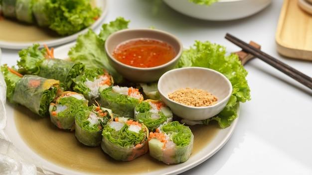 Schließen sie herauf ansicht der vietnamesischen frühlingsrollen der asiatischen vorspeise, die mit dip-soße auf esstisch serviert werden