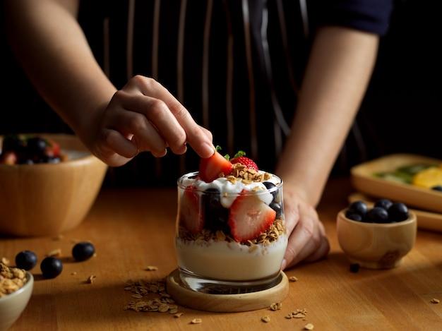 Schließen sie herauf ansicht der weiblichen hand, die erdbeere auf einer schüssel müsli mit griechischem joghurt und beeren verziert