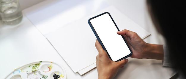 Schließen sie herauf ansicht der weiblichen künstlerhände unter verwendung des smartphones mit leerem bildschirm in ihrer werkstatt