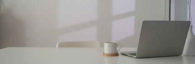 Schließen sie herauf ansicht des arbeitsbereichs mit laptop, kaffeetasse und kopierraum auf weißem tisch neben fenster