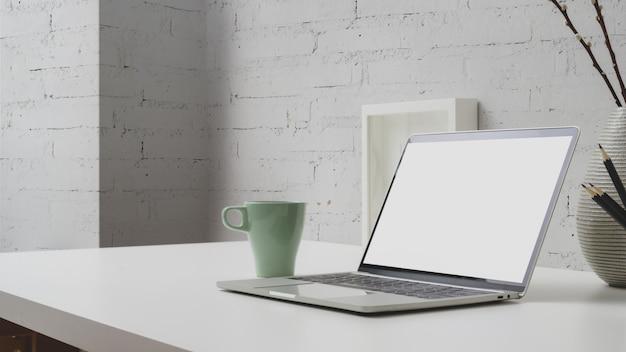 Schließen sie herauf ansicht des arbeitsbereichs mit leerem bildschirm laptop, kaffeetasse und dekorationen auf withe schreibtisch mit backsteinmauer