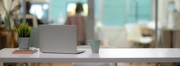 Schließen sie herauf ansicht des bequemen schreibtischs mit laptop, becher, baumtopf, büromaterial und kopierraum