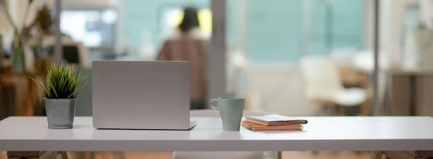 Schließen sie herauf ansicht des bequemen schreibtischs mit laptop, becher, baumtopf, notizbücher und kopienraum auf weißem tisch