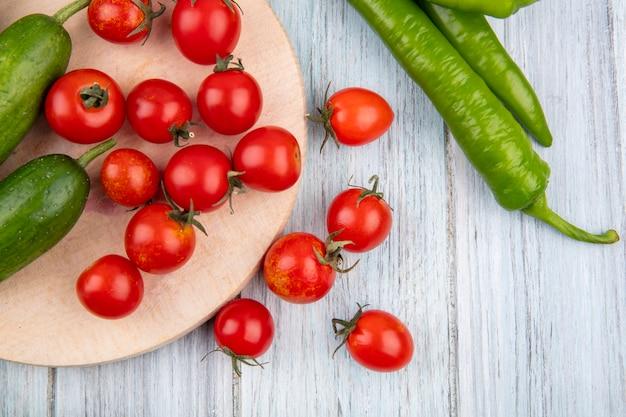 Schließen sie herauf ansicht des gemüses als gurke und tomaten auf schneidebrett mit pfeffer auf holzwand