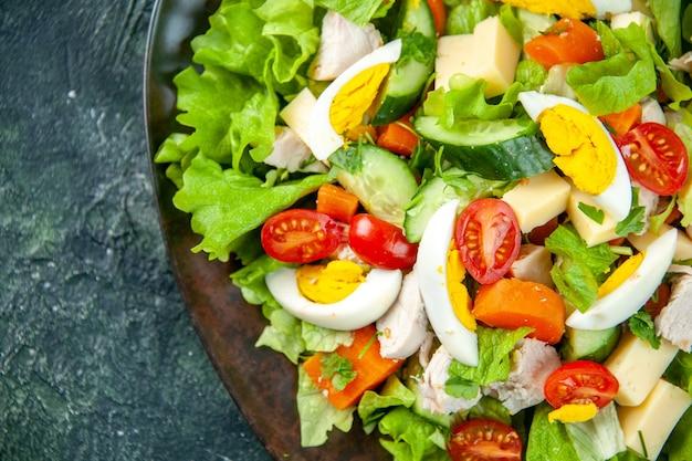 Schließen sie herauf ansicht des hausgemachten köstlichen salats in einem schwarzen teller auf der linken seite auf grünem schwarzem mischfarbenhintergrund mit freiem raum