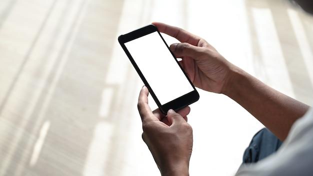 Schließen sie herauf ansicht des jungen mannes, der mit gekreuzten beinen im wohnzimmer sitzt und smartphone verwendet.