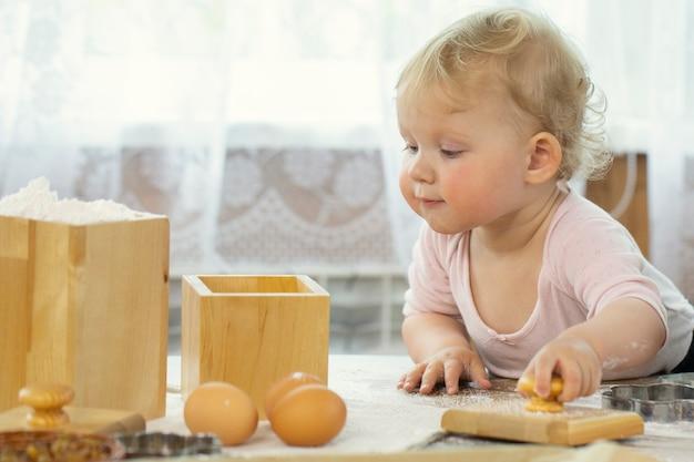 Schließen sie herauf ansicht des kleinen niedlichen babys, das auf küche kocht und hausgemachtes gebäck macht