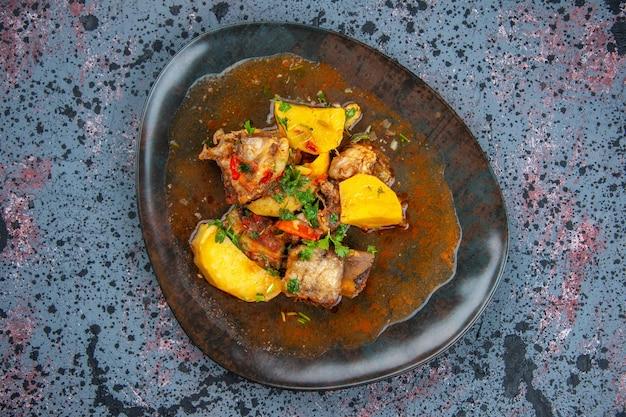 Schließen sie herauf ansicht des köstlichen abendessens mit fleischkartoffeln, die mit grün auf mischfarbenhintergrund serviert werden