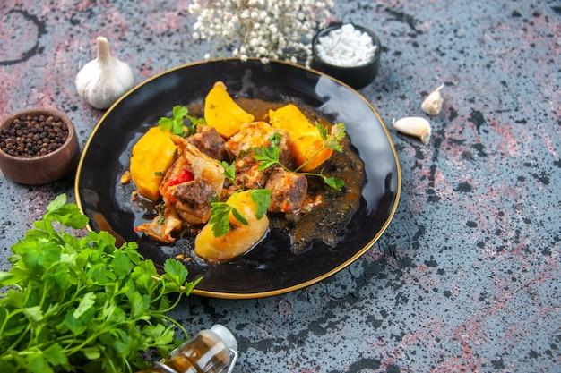 Schließen sie herauf ansicht des köstlichen abendessens mit fleischkartoffeln, die mit grün in einem schwarzen teller und gefallenen ölflaschenblume der knoblauchgewürze auf mischfarbenhintergrund serviert werden
