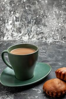 Schließen sie herauf ansicht des köstlichen kaffees und zwei kuchen in einer grünen tasse auf grau