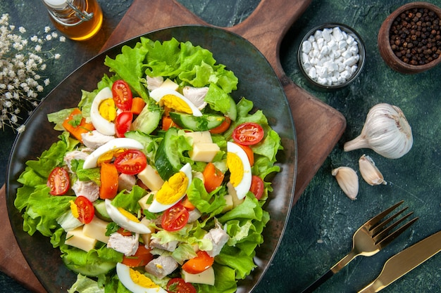Schließen sie herauf ansicht des köstlichen salats mit vielen frischen bestandteilen auf hölzernem schneidebrettgewürzölflaschen-knoblauchbesteck, das auf schwarzgrünem mischfarbenhintergrund eingestellt wird