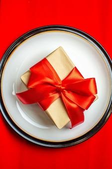 Schließen sie herauf ansicht des nationalen weihnachtsmahlzeithintergrundes mit geschenk mit bogenförmigem rotem band auf leeren tellern auf einer roten serviette auf schwarzem hintergrund