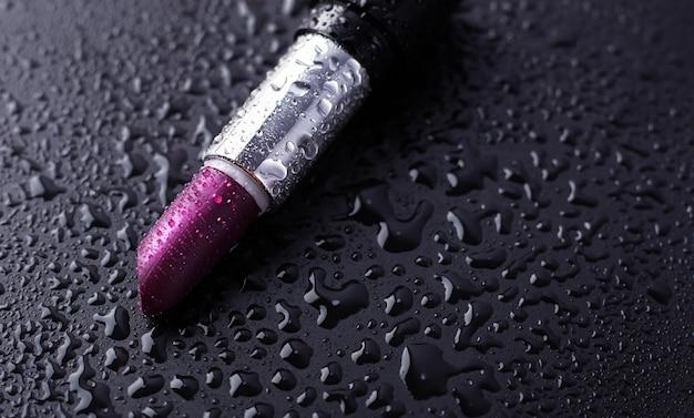 Schließen sie herauf ansicht des roten nassen lippenstifts auf schwarzem hintergrund