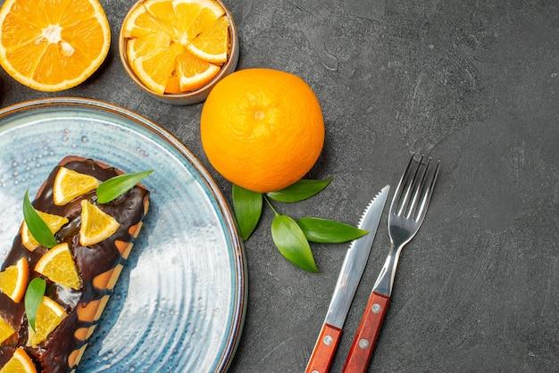 Schließen sie herauf ansicht des satzes der gelben ganzen und geschnittenen orangen-leckeren kuchen auf dunklem tisch