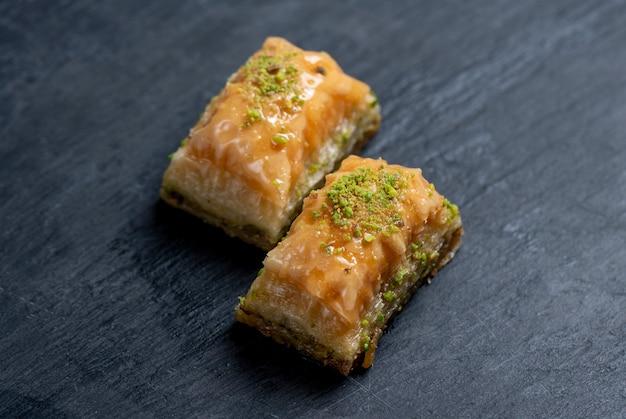 Schließen sie herauf ansicht des traditionellen türkischen baklava mit pistazie auf einer schwarzen tafel
