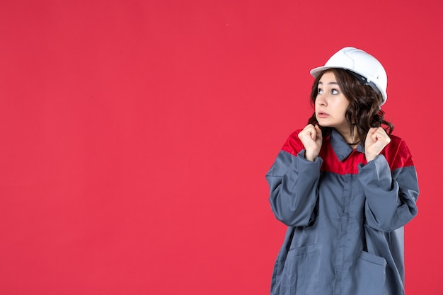Schließen sie herauf ansicht des verwirrten baumeisters in der uniform mit schutzhelm auf isolierter roter wand