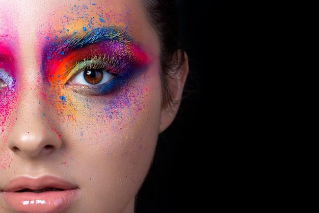 Schließen sie herauf ansicht des weiblichen gesichts mit hellem mehrfarbigem mode-make-up. holi indian color festival inspiriert