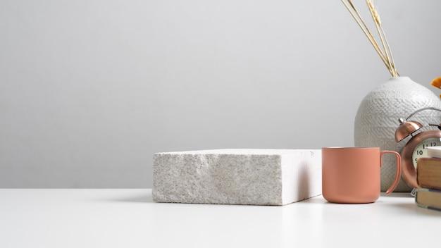Schließen sie herauf ansicht des weißen tisches mit stein, becher, vorräten, pflanzenvase und kopierraum im home-office-raum