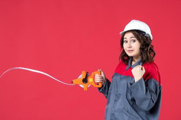 Schließen sie herauf ansicht des zuversichtlichen weiblichen architekten in der uniform mit dem schutzbandöffnungsmaßband an der roten wand