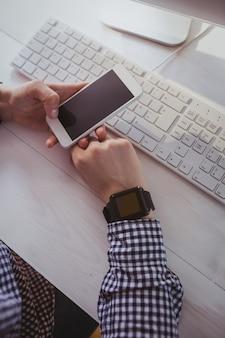 Schließen sie herauf ansicht einer geschäftsfrau, die ihren smartphone an ihrem schreibtisch im büro verwendet