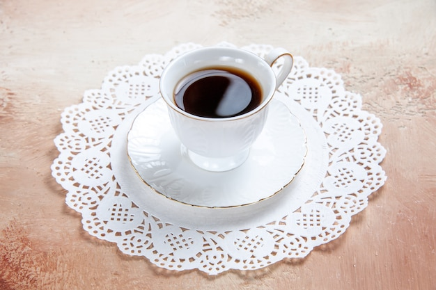 Schließen sie herauf ansicht einer tasse schwarzen tees auf einer weißen verzierten serviette auf buntem