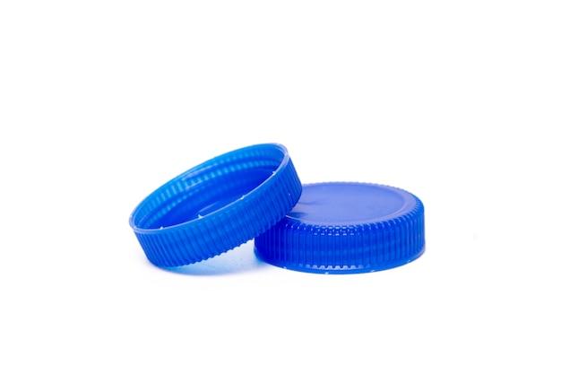 Schließen sie herauf ansicht eines bündels blauer plastikkappen von den flaschen wasser, die auf einem weißen hintergrund lokalisiert werden.