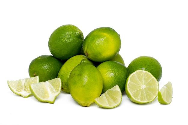 Schließen sie herauf ansicht eines bündels kalkfrüchte, die auf einem weißen hintergrund lokalisiert werden.