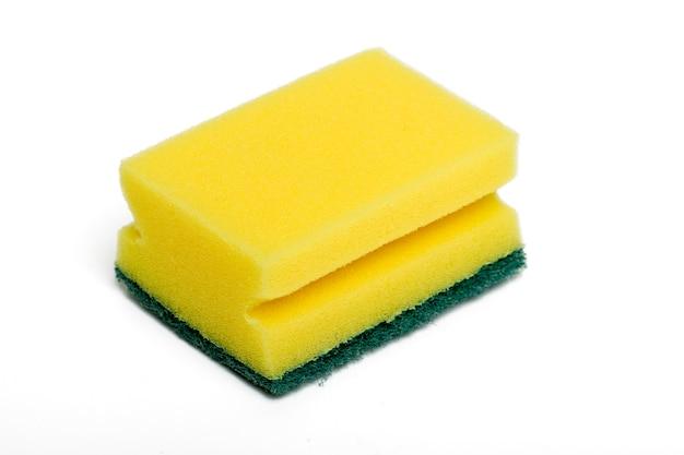Schließen sie herauf ansicht eines gelben reinigungsschwammes, der auf einem weißen hintergrund lokalisiert wird.