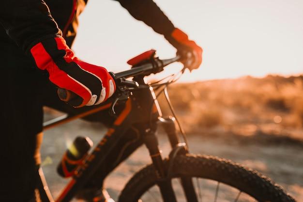 Schließen sie herauf ansicht eines radfahrerausrüstungshandschuhs und -lenkstabs. mann, der das fahrrad hinunter rocky hill bei sonnenuntergang reitet. extremsport-konzept.
