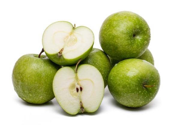 Schließen sie herauf ansicht eines stapels der grünen äpfel, die auf einem weißen hintergrund lokalisiert werden.