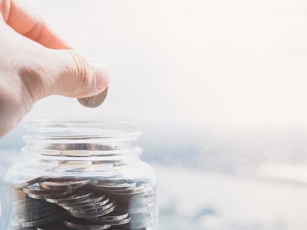 Schließen sie herauf ansicht über die seite der hand, die eine münze hält, um geld in eine glasflasche einzusetzen