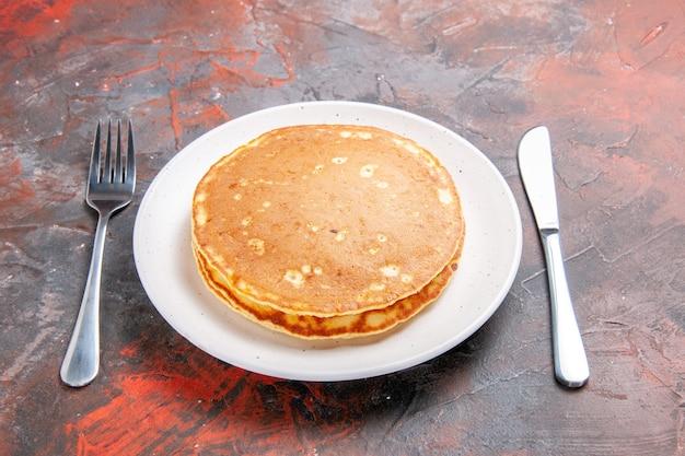Schließen sie herauf ansicht von buttermilchpfannkuchen auf einem weißen teller und messer mit gabel auf gemischter farbe