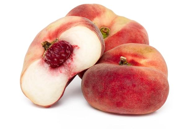 Schließen sie herauf ansicht von den geschmackvollen paraguayo-pfirsichen, die auf einem weißen hintergrund lokalisiert werden.