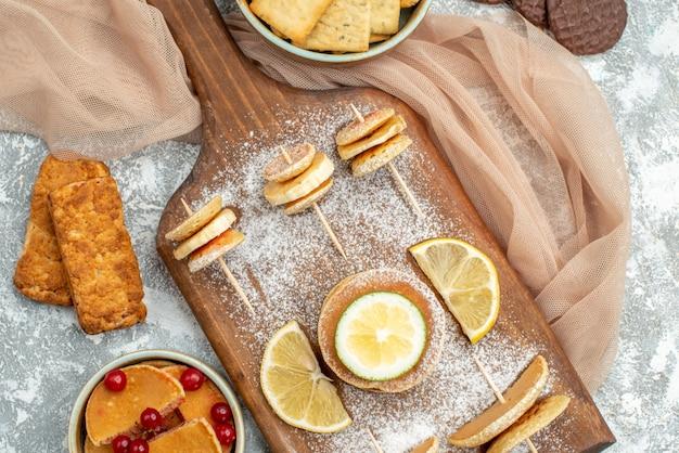 Schließen sie herauf ansicht von einfachen pfannkuchen mit zitronen auf schneidebrett und keksen orange handtuch auf blau