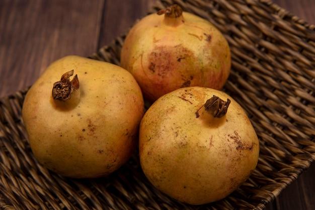 Schließen sie herauf ansicht von frischen gelben granatäpfeln auf einem weidentablett auf einer hölzernen oberfläche