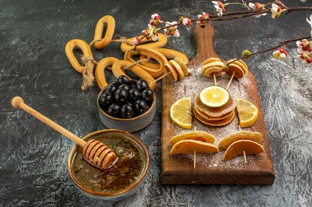 Schließen sie herauf ansicht von fruchtpfannkuchenplätzchen nahe honig in einer schüssel und schwarzen kirschen auf grauem tisch