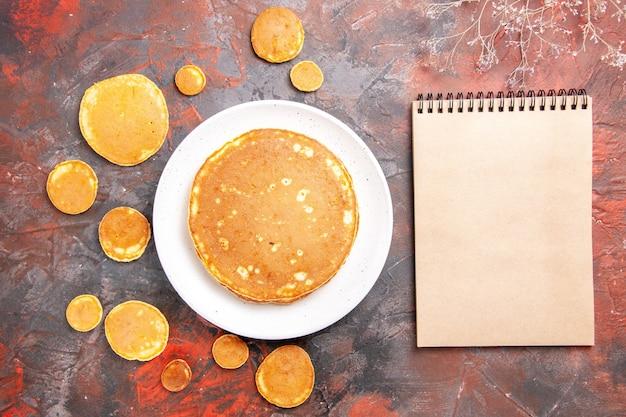 Schließen sie herauf ansicht von hausgemachten pfannkuchen auf einem weißen teller oder auf gemischtem farbtisch und notizbuch gelegt