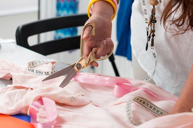 Schließen sie herauf ansicht von weiblichen schneiderinnenhänden, die etwas schneiden. die schneiderin arbeitet in ihrem atelier. handgemachte kleidung