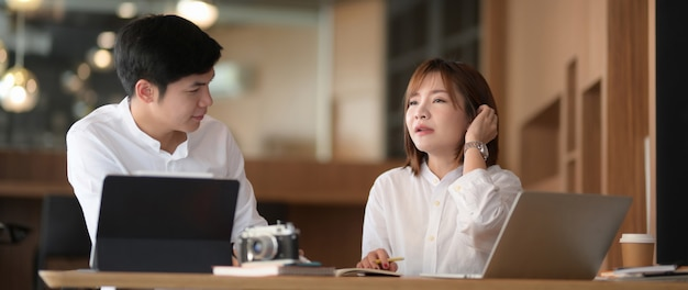Schließen sie herauf ansicht von zwei geschäftsleuten, die über ihre arbeit mit computer-laptop diskutieren