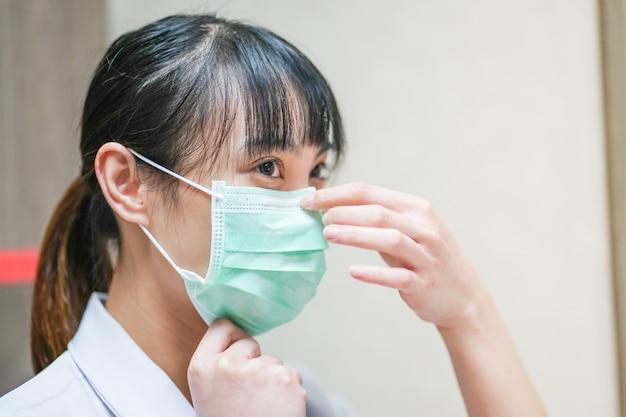 Schließen sie herauf asiatische ärztin, die medizinische maske trägt