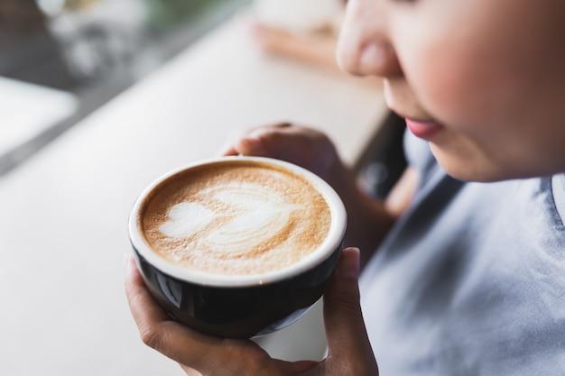 Schließen sie herauf asiatische frauen trinken morgens café des cappuccinokaffees