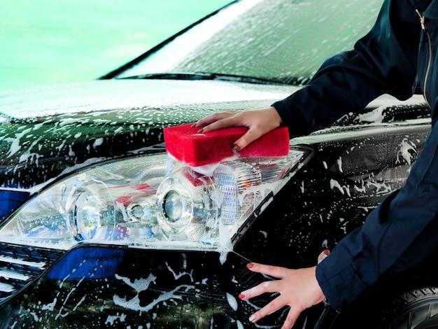 Schließen sie herauf asiatische frauenhände der arbeitskräfte, die vor auto mit schaum an der garage waschen.