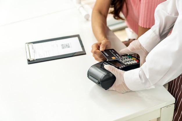 Schließen sie herauf asiatische kundin machen kontaktlose kreditkartenzahlung nach dem essen in neuem normalem sozialem fernrestaurant, um berührungen zu reduzieren. online kontaktloses und technologisches konzept.