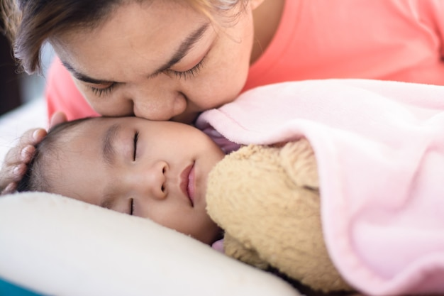 Schließen sie herauf asiatische mutter, die ihr baby küsst, das auf dem bett schläft.