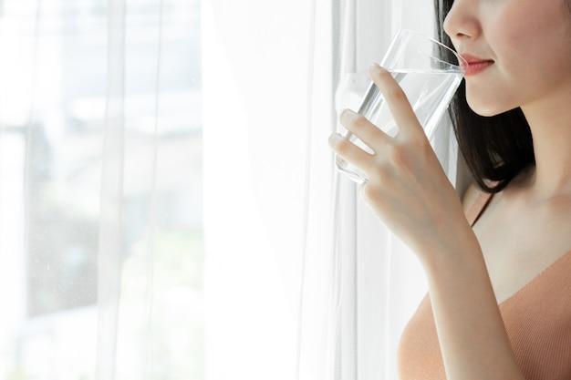 Schließen sie herauf asiatisches nettes mädchen der schönheitsfrau das gefühl glücklich, sauberes getränkwasser für gute gesundheit morgens zu trinken