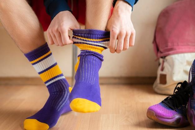 Schließen sie herauf athleten im umkleideraum, der socken anzieht und tragen sie sportkleidung